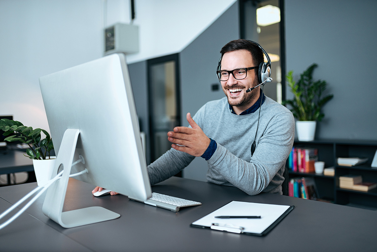 Tech support worker using cloud hosted phone system softphone, helping and instructing a customer using a headset